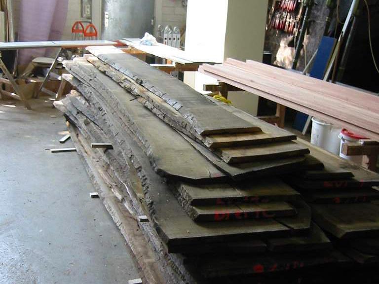 Sind die Bretter fertig zur weiteren Bearbeitung, werden sie uns geliefert. Noch ist an den Brettern die Baumrinde deutlich sichtbar.